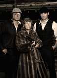 Dangerous people. A grandmother with a fur jacket holding a shotgun and two Mafia bodyguards standing behind her Royalty Free Stock Photography