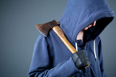 Dangerous person with an axe, thug. A dangerous female with a hooded sweater holding an axe Royalty Free Stock Photography