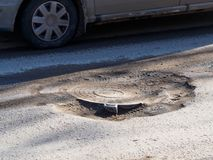 Dangerous pit on the road. In Russian town Stock Photos