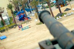Dangerous Playground. Angled shot of a playground in the distance, with a cannon in the foreground pointed toward it.  Focus is on the playground.  Conceptual Stock Photography