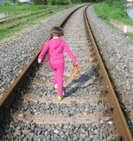 Dangerous playing. Little girl playing on railroad tracks Royalty Free Stock Image