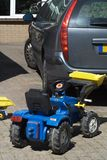 Dangerous playing area. Dangerous situation with kids play tractor on street behind a car royalty free stock photo