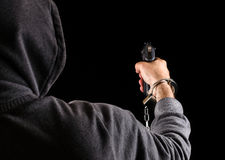 Dangerous prisoner fugitive with a Gun. Dangerous handcuffed prisoner fugitive with gun royalty free stock photography