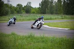 Dangerous race between two motorcycle athletes stock photo