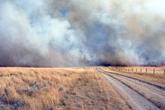 Dangerous road. Back road blocked by fire and smoke stock image