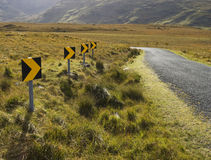 Dangerous road curve signs. A dangerous curve on the road with black and yellow signs royalty free stock photos