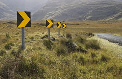Dangerous road curve signs. A dangerous curve on the road with black and yellow signs Stock Images
