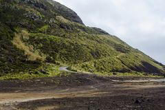 Dangerous road on hill with many curves and inclination in volcanic area royalty free stock photography