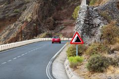 Dangerous road in the mountains. The car moves in the mountains along the road with dangerous turns Stock Photo