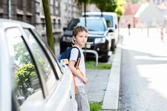 Dangerous road to school. Little schoolboy waiting for the opportunity to move to the other side of the street. Road to school Royalty Free Stock Photos