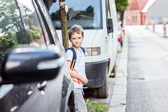 Dangerous road to school. Little schoolboy waiting for the opportunity to move to the other side of the street. Road to school Royalty Free Stock Images