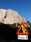 Dangerous rocky road in Slovenia. Rocky road sign under Pristojnik mountain on the way down from Vrsic mountain pass Stock Photos