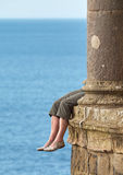 Dangerous seat. A girl sitting on the window sill of Mussenden Temple  near Castlerock, Antrim, Northern Ireland, her feet dangling 40 meters over the ground Royalty Free Stock Photography