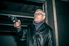 Dangerous senior with a gun. Dangerous senior man aiming a gun and standing in old dark cabin stock images