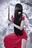 Dangerous sexual mystery asian girl. Anime style. Woman with long black hair with sword and red seductive dress Royalty Free Stock Images