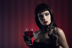 Dangerous sexy vampire girl with glass of wine or blood Stock Image