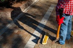 Man with ax gives ominous shadow. Dangerous shadow. A man in a red checkered shirt holds an ax in his hand in the yard. A deceptive shadow falls from him royalty free stock images