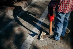 Man with ax gives ominous shadow. Dangerous shadow. A man in a red checkered shirt holds an ax in his hand in the yard. A deceptive shadow falls from him stock photo