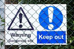Dangerous site warning sign keep out behind wire fence. Uk royalty free stock photography