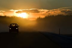 Dangerous situation. Fog on the road at the start of winter. Bright sun in clouds, minivan on the left side of road and dangerous overtaking in the background Royalty Free Stock Photos
