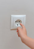 Dangerous situation at home. Child sticks his fingers in the socket. Dangerous situation at home stock photography