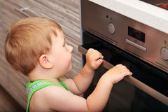 Dangerous situation in the kitchen. Child playing with electric oven Stock Photo