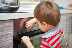 Dangerous situation in the kitchen. Child playing with electric oven Royalty Free Stock Images