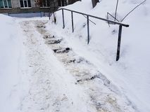Dangerous slippery stairs and old handrail in winter. Dangerous slippery stairs and old handrail in the winter in the snow royalty free stock photo
