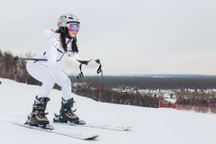 Dangerous sport. woman in white sportswear enjoying skiing royalty free stock photography