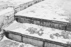 Dangerous stone staircase under the snow in winter. Ice in the city on the sidewalk royalty free stock photography