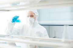 Dangerous substance. Young scientist holding tube with toxic substance Stock Photo