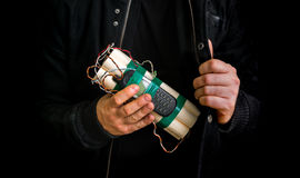 Dangerous terrorist in black jacket with dynamite bomb in hand Stock Photos