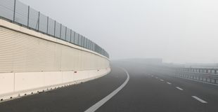 Dangerous thick fog near the sharp curve of the highway. Very dangerous thick fog near the sharp curve of the highway in winter stock image