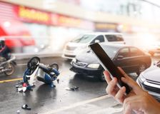 Woman hands using smartphone calling ambulance and car insurance service. Dangerous traffic on the road, Careless driving car collides with motorcycle. Woman royalty free stock image