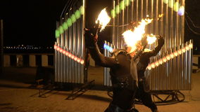 Dangerous tricks with fire poi. Two guys are holding a fire poi near the face at the night fire show stock video