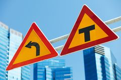Dangerous turn left and crossing roads. Warning traffic signs over blue city skyline stock images