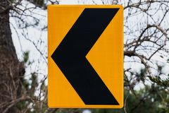 Dangerous turn left, yellow black road sign. Mounted on roadside stock photo