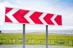 Dangerous turn. Road sign in summer city Stock Image