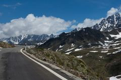 Dangerous turned road high in the Alps between melting snow Stock Photo