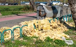 Dangerous waste material dumped on the urban city street near garbage cans polluting and littering environment with hazard junk. Waiting for dumpster truck to stock photo