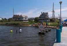 Dangerous Waters. Seaside Heights, NJ USA -- August 21, 2017 Young people are crabbing in shallow waters by a danger sign in Seaside Heights at the Jersey Shore Stock Photo
