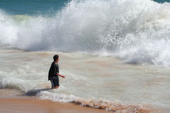 Dangerous waves. Boy stands at shore with dangerous wave approaching Royalty Free Stock Photo