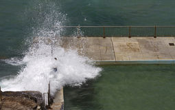 Dangerous waves breaking over rock pool Stock Photography
