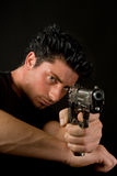 Dangerous weapon. Young man aiming and firing a deadly weapon Royalty Free Stock Images