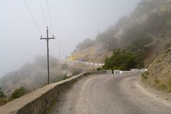 Dangerous winding road in the mountains in a fog. stock photography