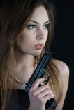 Dangerous woman. Beautiful woman holding a gun in her hand Royalty Free Stock Photo