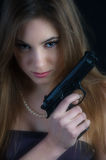 Dangerous woman. Beautiful woman with a gun in her hand royalty free stock image