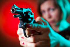 Dangerous woman. With a gun in her hands (focus on the weapon Stock Photography