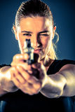 Dangerous woman terrorist dressed in black with a gun in her han. Ds Royalty Free Stock Images