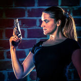 Dangerous woman terrorist dressed in black with a gun in her han Stock Images